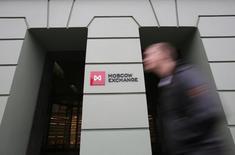 Человек проходит мимо здания Московской биржи 7 ноября 2014 года. Российские фондовые индексы резко снизились во вторник с возобновлением торгов после длинных выходных, за время которых агентство Moody's опустило кредитный рейтинг РФ до спекулятивного уровня. REUTERS/Maxim Shemetov