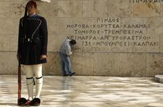 """A presidential """"Evzon"""" stands guard (L) as Giorgos Paganis, 52, a marble craftsman from the island of Tinos, adds the words """"Mediterranean"""" and """"Aegean"""" onto the Tomb of the Unknown Soldier, under a list of places where Greeks fought modern history battles, outside the parliament in central Athens, February 24, 2015.   REUTERS/Yannis Behrakis"""