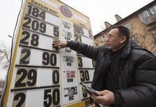 Работник пункта обмена валюты меняет курсы в Алма-Ате. 24 февраля 2015 года. В ожидании вероятных досрочных президентских выборов Казахстан отказывается девальвировать тенге, однако опасность возможной переоценки валюты уже очевидна и может в конечном счете подтолкнуть власти к действиям. REUTERS/Shamil Zhumatov
