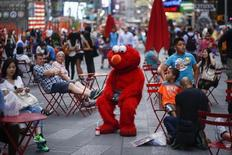 Jorge, an immigrant from Mexico, dressed as the Sesame Street character Elmo rests in Times Square, New York July 29, 2014.  REUTERS/Eduardo Munoz