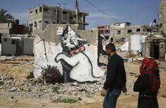 Palestinians walk past a mural of a playful-looking kitten, presumably painted by British street artist Banksy, on the remains of a house that witnesses said was destroyed by Israeli shelling during a 50-day war last summer, in Biet Hanoun town in the northern Gaza Strip February 26, 2015. REUTERS/Suhaib Salem