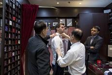 Tailors measure a customer inside a bespoke tailoring firm at Hong Kong's Tsim Sha Tsui shopping district February 14, 2015.      REUTERS/Tyrone Siu
