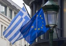 A Greek (L) and a European flag flutter outside the Greek embassy in Brussels February 19, 2015.  REUTERS/Yves Herman