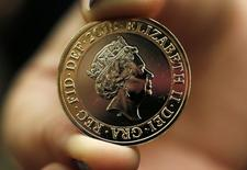 A gallery assistant holds a 2-pound coin with the new portrait of Britain's Queen Elizabeth following it's unveiling at the National Portrait Gallery in London March 2, 2015.  REUTERS/Suzanne Plunkett
