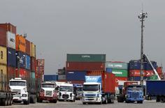 Unos camiones y contenedores en el puerto de Santos, Brasil, feb 25 2015. Brasil registró su mayor déficit comercial para febrero desde que se tienen registros, debido a una continua baja en los precios de exportaciones clave, mostraron el lunes datos del Gobierno.     REUTERS/Paulo Whitaker