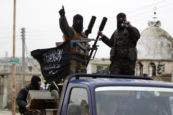 Members of al Qaeda's Nusra Front gesture as they drive in a convoy touring villages, which they said they have seized control of from Syrian rebel factions, in the southern countryside of Idlib, December 2, 2014. Picture taken December 2, 2014. REUTERS/Khalil Ashawi