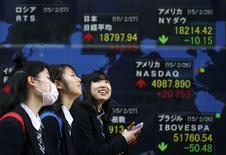 Студентки у брокерской конторы в Токио. 27 февраля 2015 года. Азиатские фондовые рынки, кроме Китая, снизились в среду за счет спада на фондовых рынках США и местных факторов. REUTERS/Toru Hanai