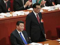 Chinese President Xi Jinping sits as Premier Li Keqiang stands next to him during the opening of the annual full session of the National People's Congress, the country's parliament, at Great Hall of the People, in Beijing, March 5, 2015. REUTERS/Barry Huang