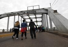 People walk along the Edmund Pettus Bridge before the beginning of the 50th anniversary of the Selma to Montgomery civil rights march in Selma, Alabama March 8, 2015. REUTERS/Tami Chappell