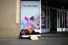Una persona durmiendo a las afueras de una farmacia en el centro de Santiago, nov 24 204. El acelerado crecimiento que ha tenido América Latina en la última década aún deja a uno de cada cinco residentes de la región viviendo con menos de 4 dólares al día, dijo el Banco Mundial en un estudio publicado el lunes. REUTERS/Ivan Alvarado