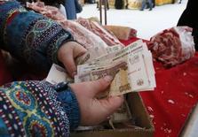 Женщина держит в руках рублевые купюры на рынке в Красноярске 14 января 2015 года.  Рубль подрос при открытии биржевых торгов среды от двухнедельных минимумов, достигнутых накануне на неликвидном вечернем рынке, поддержкой могут выступать утренние продажи экспортной выручки, в целом же сейчас преобладают негативные для российской валюты факторы, которые могут взять верх в течение дня, по оценкам участников рынка. REUTERS/Ilya Naymushin