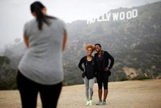Hikers pose for a photo in front of the Hollywood sign on a foggy day in Los Angeles, California January 20, 2015. REUTERS/Lucy Nicholson
