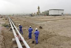 Рабочие на нефтяном месторождении Западная Курна в Басре. 13 октября 2014 года. У Ирака возникла задолженность перед иностранными компаниями, разрабатывающими его месторождения, а бюджетные доходы снижаются из-за падения цен на нефть. REUTERS/Essam Al-Sudani