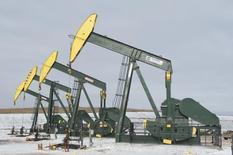 Станки-качалки близ Уиллистона, Северная Дакота 12 ноября 2014 года.  Цены на нефть растут после снижения накануне, но этому препятствует стабилизация курса доллара. REUTERS/Andrew Cullen