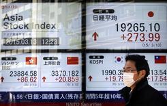 Прохожий у брокерской конторы в Токио. 13 марта 2015 года. Азиатские фондовые рынки выросли в пятницу и завершили неделю разнонаправлено. REUTERS/Yuya Shino