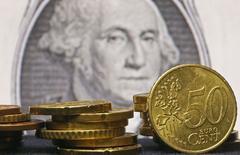 Imagen de monedas de euro frente a un billete de un dólar tomada en Zenica en Bosnia. 13 de marzo de 2015.  La baja del euro hacia la paridad con el dólar dará un muy deseado impulso a las empresas europeas este año y forzará a que sus rivales estadounidenses adapten sus negocios o se arriesguen a perder participación de mercado. REUTERS/Dado Ruvic