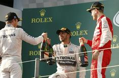 (L to R) Second placed Mercedes Formula One driver Nico Rosberg of Germany, race winner Mercedes Formula One driver Lewis Hamilton of Britain and third placed Ferrari Formula One driver Sebastian Vettel of Germany celebrate on the podium after the Australian F1 Grand Prix at the Albert Park circuit in Melbourne March 15, 2015.    REUTERS/Jason Reed