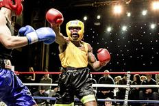 Amateur boxer Shepard Davis with the FDNY Bravest Boxing team throws a punch at an opponent at a charity event at Webster Hall in New York, in this handout picture taken March 6, 2014.   REUTERS/JJ Ignotz/Handout via Reuters