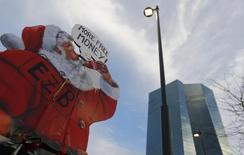 Плакат участников акции протеста у штаб-квартиры ЕЦБ. Франкфурт-на-Майне. 22 ноября 2014 года. Тысячи людей могут выйти на улицы Франкфурта-на-Майне в среду, чтобы выразить протест против мер жесткой экономии, в которых они винят Европейский центробанк. REUTERS/Kai Pfaffenbach