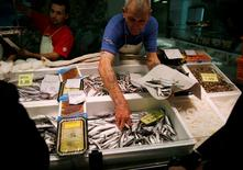 Fishmongers sell fish at a market in central Madrid November 13, 2014. REUTERS/Andrea Comas