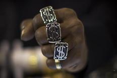 Кольца с символами американского доллара на руке мужчины в Нью-Йорке 6 ноября 2014 года. Курс доллара малоподвижен незадолго до публикации заявления ФРС по итогам совещания, от которого инвесторы ожидают новой информации о предстоящем повышении процентных ставок, первом почти за девять лет. REUTERS/Mike Segar