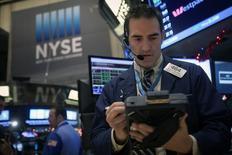 Трейдер на торгах Нью-Йоркской биржи 29 декабря 2014 года. Американские фондовые индексы S&P 500 и Dow Jones снизились во вторник накануне публикации заявления ФРС.  REUTERS/Carlo Allegri