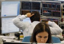 Трейдеры в торговом зале инвестбанка Ренессанс Капитал в Москве 9 августа 2011 года. Российские фондовые индексы снижаются при открытии рынка в пятницу, и ММВБ вплотную приблизился к психологической поддержке на уровне 1.600 пунктов. REUTERS/Denis Sinyakov