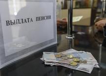 Окошко для выплаты пенсий в почтовом отделении в Симферополе. 25 марта 2014 года. Кремль оставил правительству право определить судьбу накопительной пенсионной системы, где собрано уже больше 3 триллионов рублей, а бизнесу непублично пообещал сохранить существующую пенсионную модель, что не исключает возможность очередного изъятия отчислений граждан в следующем году. REUTERS/Shamil Zhumatov