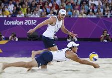 Brazil's Emanuel (R) returns the ball watched by teammate Alison during their men's beach volleyball gold medal match against Germany's Julius Brink and Jonas Reckermann at Horse Guards Parade during the London 2012 Olympic Games August 9, 2012.   REUTERS/Marcelo Del Pozo