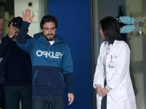 McLaren's Formula One driver Fernando Alonso of Spain waves to the media as he leaves the hospital where he was hospitalized since Sunday in Sant Cugat after crashing during a test session February 25, 2015. REUTERS/Albert Gea