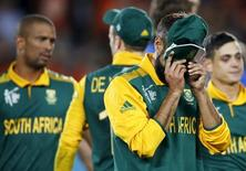 South Africa's Imran Tahir covers his face with his cap as he reacts next to his teammates after New Zealand won their Cricket World Cup semi-final match in Auckland, March 24, 2015.  REUTERS/Nigel Marple