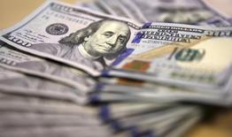 En la imagen, billetes de 100 dólares son exhibidos en Johannesburgo. 13 de agosto, 2014. Los planes de inversión de las empresas estadounidenses bajaron por sexto mes seguido en febrero, probablemente afectados por la fortaleza del dólar y la débil demanda global, mostró el miércoles un reporte del Departamento de Comercio. REUTERS/Siphiwe Sibeko