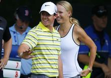 Rory McIlroy of Northern Ireland and his former girlfriend, tennis player Caroline Wozniacki of Denmark, wait at the fourth tee during the final round of the Deutsche Bank Championship golf tournament in Norton, Massachusetts September 2, 2013.  REUTERS/Brian Snyder