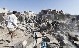 Люди ищут выживших под обломками домов, попавших под авиаудары, близ аэропорта Саны. 26 марта 2015 года. Саудовская Аравия и ее ближневосточные союзники начали в четверг военные действия, в том числе нанесли авиаудары, по территории Йемена, чтобы остановить продвижение поддерживаемых Ираном сил на юге страны. REUTERS/Khaled Abdullah