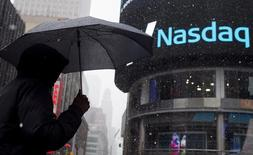 Мужчина с зонтом у здания Nasdaq MarketSite в Нью-Йорке . 20 марта 2015 года. Дубайский биржевой холдинг Borse Dubai, накануне продавший пакет в LSE, не имеет в настоящее время намерения продавать принадлежащей ей пакет Nasdaq OMX Group, сказал Рейтер представитель дубайской компании. REUTERS/Adrees Latif