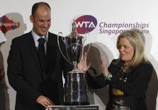 Stacey Allaster (R), Chairman and Chief Executive Officer of the Women's Tennis Association (WTA), gestures next to World Sports Group's Chief Operating Officer Andrew Georgiou as they prepare to pose with the Billie Jean King trophy after a WTA announcement in Singapore May 8, 2013. REUTERS/Edgar Su