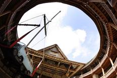 A camper van is lifted by a crane to be placed on the stage at London's Globe theatre June 17, 2007. REUTERS/Alessia Pierdomenico
