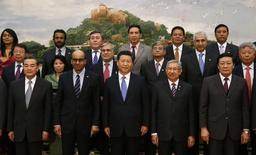 China's President Xi Jinping (front C) poses for photos with guests at the Asian Infrastructure Investment Bank launch ceremony at the Great Hall of the People in Beijing October 24, 2014.  REUTERS/Takaki Yajima/Pool