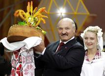 Президента Белоруссии Александра Лукашенко приветствуют хлебом и солью во время праздника урожая в городе Горки. 21 сентября 2012 года. Белоруссия во вторник выплатила $75,9 миллиона Международному валютному фонду, полностью рассчитавшись по кредиту на $3,5 миллиарда, который был выдан в 2009-2010 годах, сообщило министерство финансов. REUTERS/Vasily Fedosenko