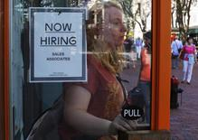 """A woman walks past a """"Now Hiring"""" sign as she leaves the Urban Outfitters store at Quincy Market in Boston, Massachusetts September 5, 2014.  REUTERS/Brian Snyder"""