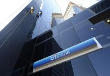 Window washers work above a logo of Citibank in downtown Buenos Aires March 17, 2015. REUTERS/Enrique Marcarian