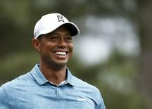 Tiger Woods of the U.S. smiles as he walks up the fourth fairway during his practice round ahead of the 2015 Masters at the Augusta National Golf Course in Augusta, Georgia April 6, 2015.  REUTERS/Jim Young