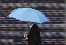 Прохожий у брокерской конторы в Токио. 7 апреля 2015 года. Азиатские фондовые рынки выросли во вторник вслед за американским рынком и за счет местных новостей. REUTERS/Issei Kato