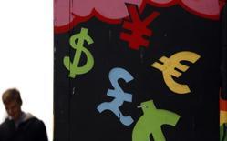 Смиволы валют у пункта обмена валют в Дублине 22 октября 2014 года. Доллар перестал расти, значительно поднявшись во вторник после спада, вызванного слабым показателем занятости в США. REUTERS/Cathal McNaughton