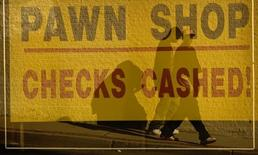 Pedestrians are reflected in the window of Pawtucket Pawnbrokers on Main Street in Pawtucket, Rhode Island December 2, 2008. REUTERS/Brian Snyder
