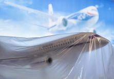Модель самолета Sukhoi Superjet SSJ-100 на авиасалоне в Фарнборо. 13 июля 2014 года. Российские власти сократили на 100 миллиардов рублей господдержку банков через ОФЗ объемом 1 триллион рублей, перераспределив эти средства в пользу Объединенной авиастроительной госкорпорации (ОАК), следует из поправок в федеральный бюджет 2015 года, принятых во втором чтении. REUTERS/Kieran Doherty