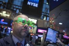 Трейдер на торгах Нью-Йоркской фондовой биржи 31 декабря 2014 года. Фондовые рынки США выросли в среду после публикации протокола мартовского совещания ФРС, показавшего, что центробанк не отказывается от намерения повысить процентные ставки в этом году.  REUTERS/Carlo Allegri
