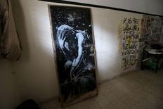 Una obra pintada por Banksy en la puerta de una casa destruída, en una galería de un palestino local en Khan Younis. Imagen de archivo, 1 abril, 2015.  La policía palestina confiscó el jueves una pintura obra del artista de graffiti Banksy realizada sobre una puerta, después de que el propietario original de la puerta, dañada por bombardeos, se quejara de que lo estafaron para que la vendiera a un bajo precio. REUTERS/Ibraheem Abu Mustafa