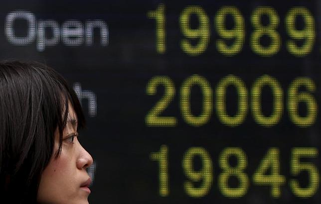 4月10日、寄り付きの日経平均は4日続伸して始まり、取引時間中としては2000年4月17日以来、約15年ぶりに2万円台を回復した。写真は都内の株価ボード(2015年 ロイター/Yuya Shino)