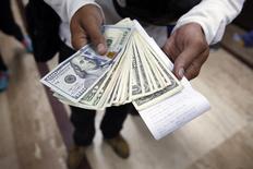Un hombre posa con dólares, luego de comprarlos en una casa de cambio en Caracas. Imagen de archivo, 24 febrero, 2015.  Venezuela redujo el viernes la cantidad de divisas a precio preferencial que se pueden comprar para viajar fuera del país, en un intento por ahorrar parte de sus disminuidos ingresos en dólares tras la caída de los precios del petróleo. REUTERS/Carlos Garcia Rawlins